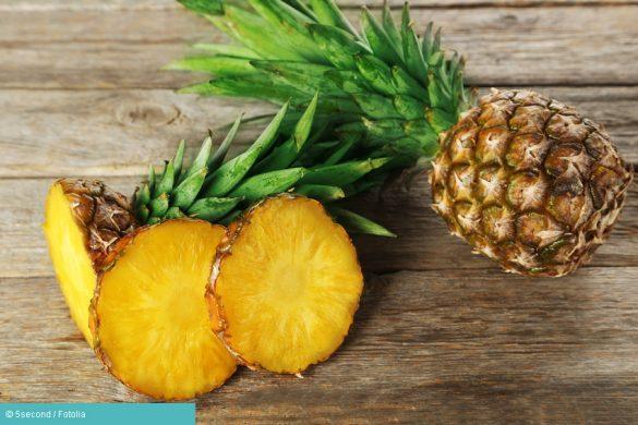 Ganze und halbe Ananas auf einem Tisch