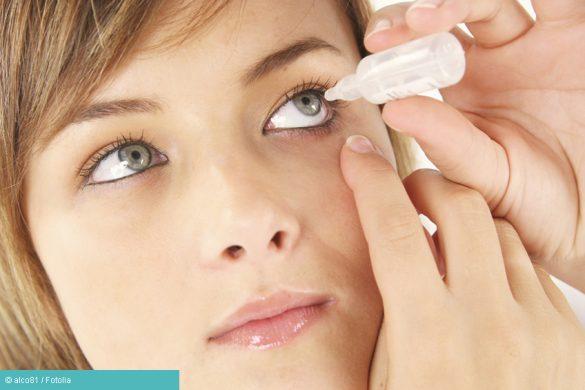 Frau behandelt sich mit Augentropfen