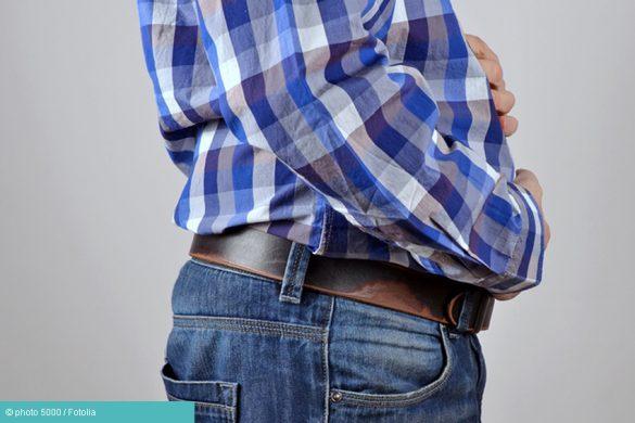 Mann hält Bauch bei Blähungen