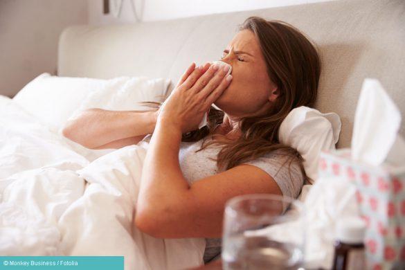 Frau mit einer Grippe putzt sich die Nase