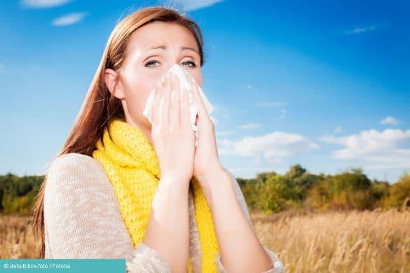 Frau mit Heuschnupfen putzt sich die Nase
