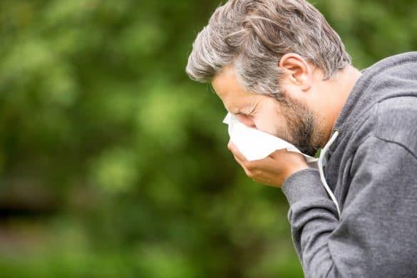 Mann mit Heuschnupfen beim Niesen