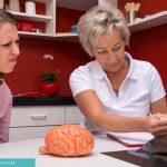 Ärztin zeigt junger Frau Röntgenaufnahmen ihres Gehirns - Multiple Sklerose