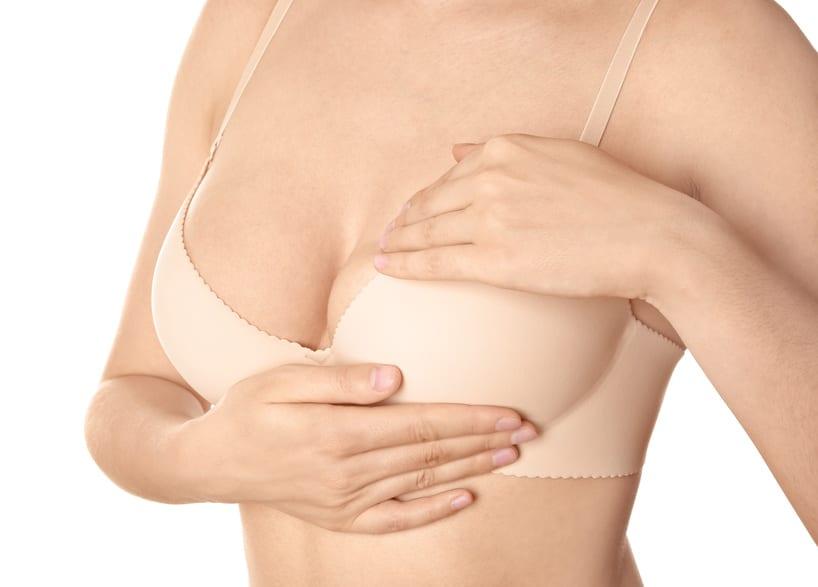 Frau überprüft Brustgröße / Mammareduktionsplastik