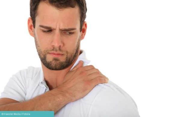 Muskelkater: Mann fasst sich an Schulter