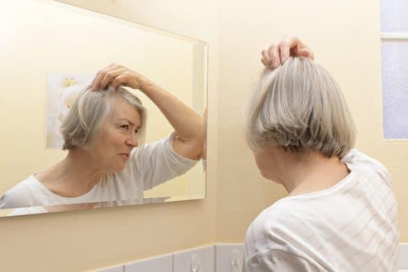 Ältere Frau überprüft Haare
