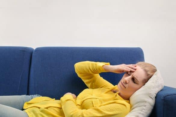 Frau mit Kopfschmerzen auf Sofa