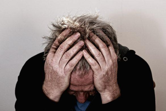 Mann hält sich Kopf wegen Kopfschmerzen