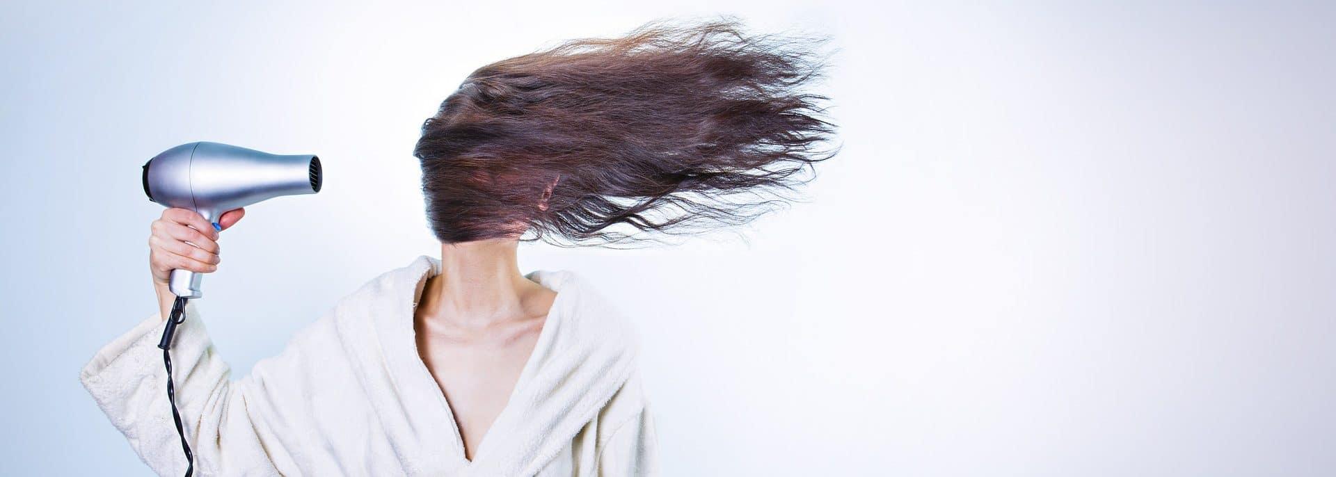 Frau fönt sich Haare