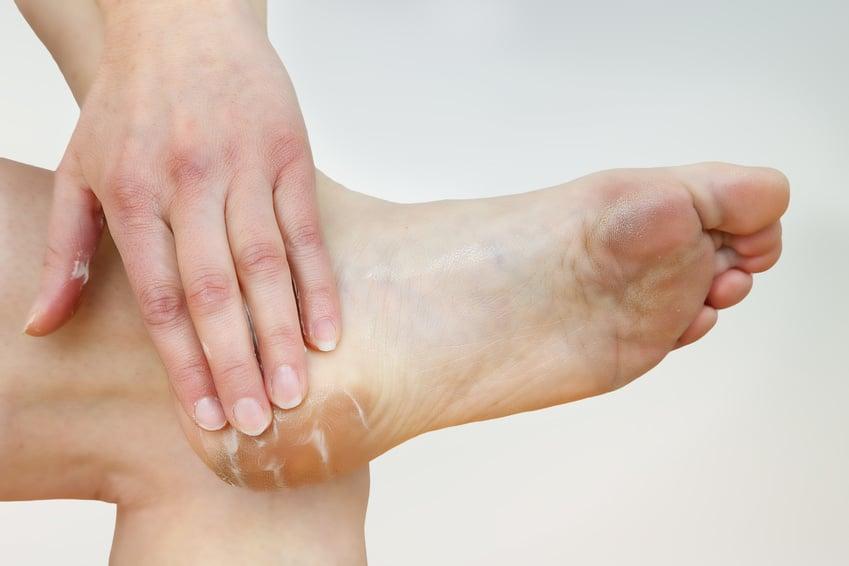 Frau reibt sich die Fußsohle