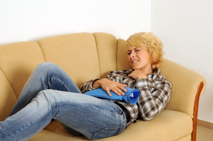 Frau mit krampfartigen Magenschmerzen auf dem Sofa