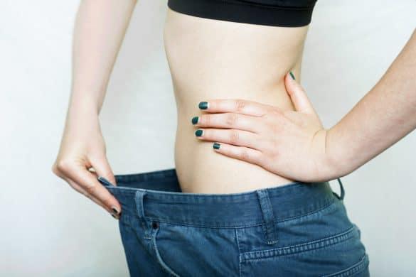 schlanke Frau mit zu großer Hose nach Diät
