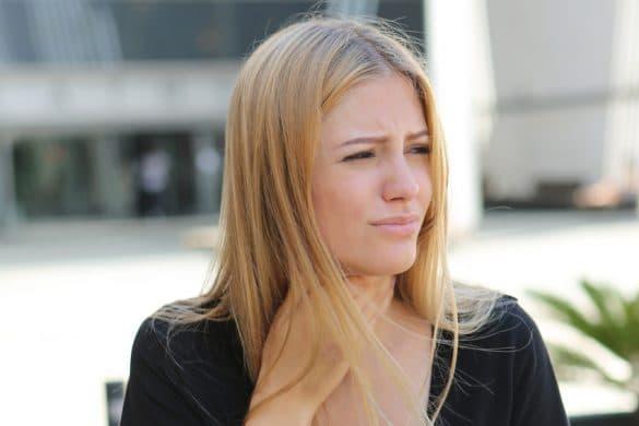 Frau fässt sich an den Hals