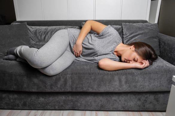 Frau mit stechenden Magenschmerzen auf dem Sofa
