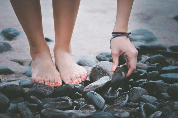 Weibliche Füße mit Fußpilz am Strand auf Felsen und Steinen
