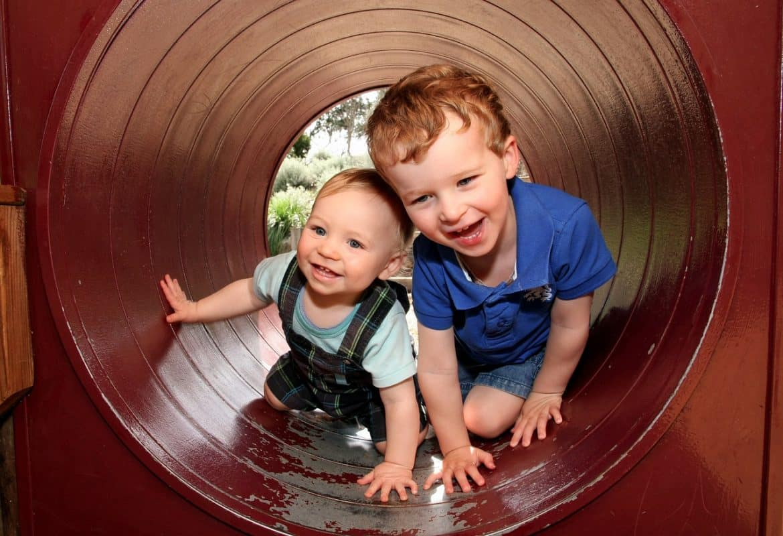 Zwei Jungen spielen im Garten mit nackten Füßen und Händen und infizieren sich mit Nagelpilz