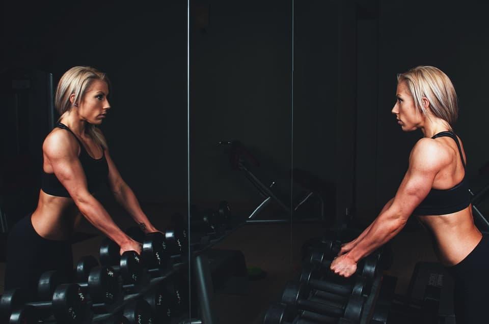 Frau mit Muskeln schaut sich im Fitnessstudio im Spiegel an