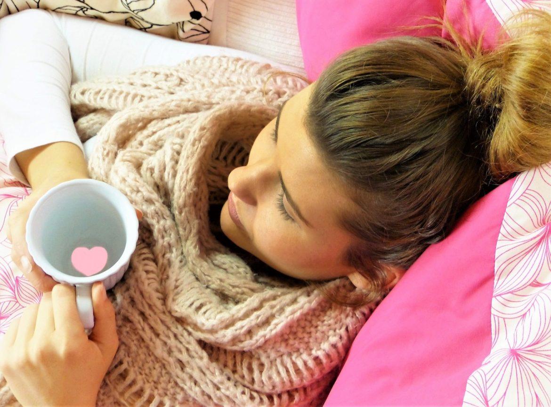 Frau liegt mit Tee auf der Couch und kuriert ihre starken Magenschmerzen aus
