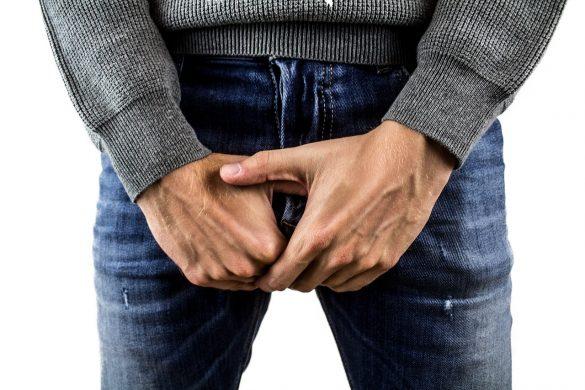 Mann hält sich die Hände vor die Geschlechtsteile da er Syphilis hat
