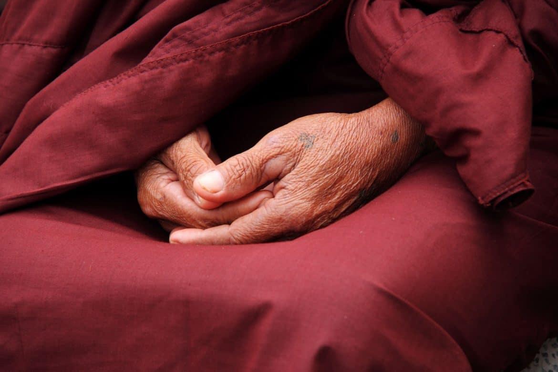 Ältere Person versteckt ihre Hände und ist einsam aufgrund des unbehandelten Nagelpilzes