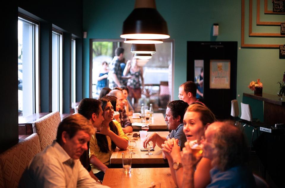 Gruppe von Menschen in einem Restaurant unterhalten sich über ihre gemeinsame Diät