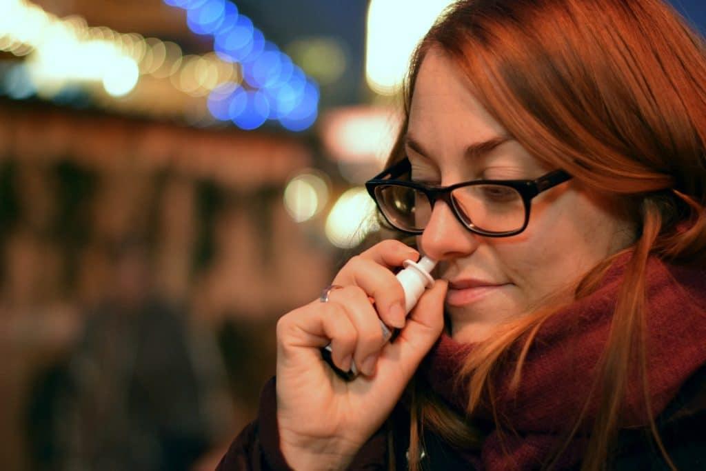 Frau mit Nasenspray