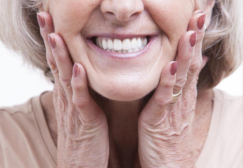 Ältere Frau zeigt Zähne