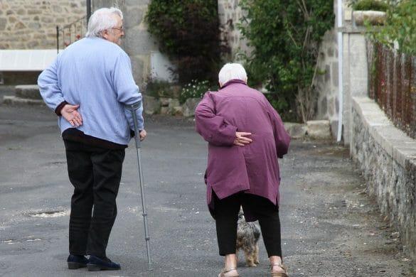 Älteres Paar mit Osteoporose läuft auf einem Hof